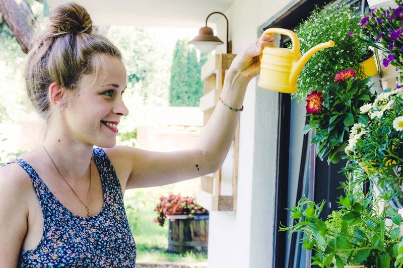 beautiful young female florist Flower Bed Potted Plants Watering Balcony Florist Watering Can Young Woman Smiling Women Happiness Lifestyles One Person Young Adult Young Women Plant Real People Nature Holding Water Outdoors