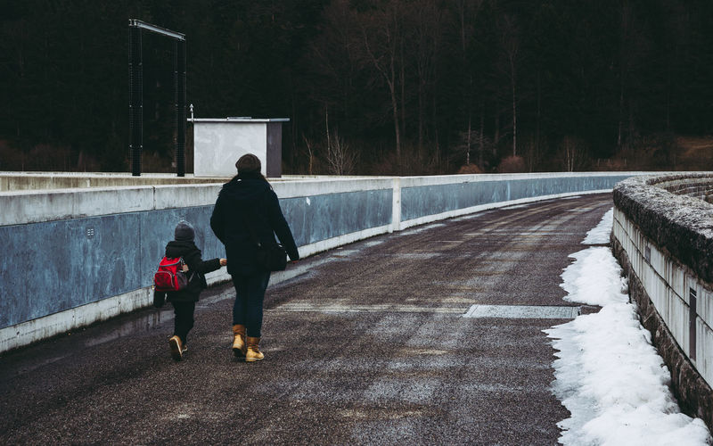 Rear View Of Mother And Daughter Walking On Road During Winter