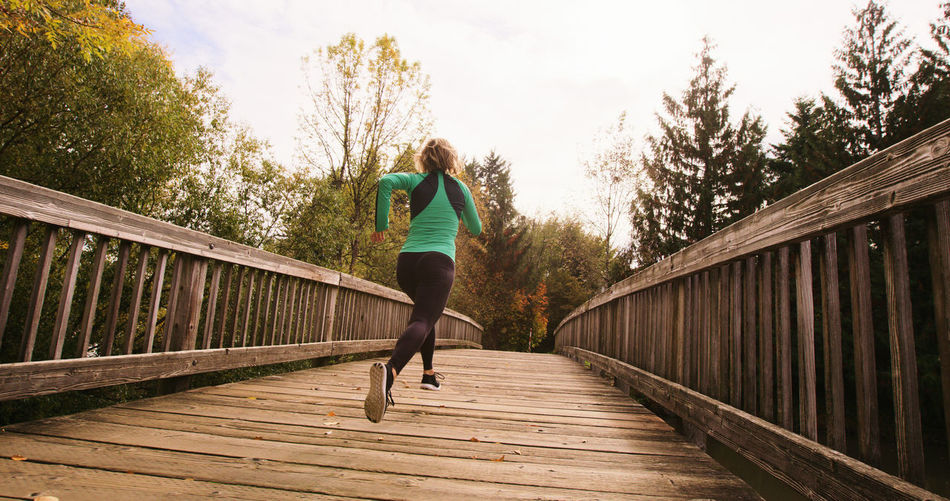 Adult Bridge - Man Made Structure Day Exercising Footbridge Full Length Healthy Lifestyle Jogging Leisure Activity Lifestyles Motion Nature One Person Outdoors Real People Running Sky Sport Sports Clothing Tree Vitality Women Wood - Material Young Adult Young Women