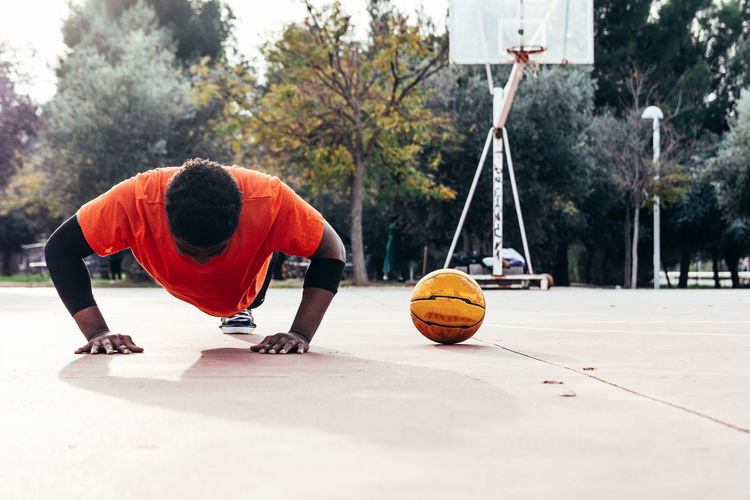 Full length of player doing push ups by ball at basketball court