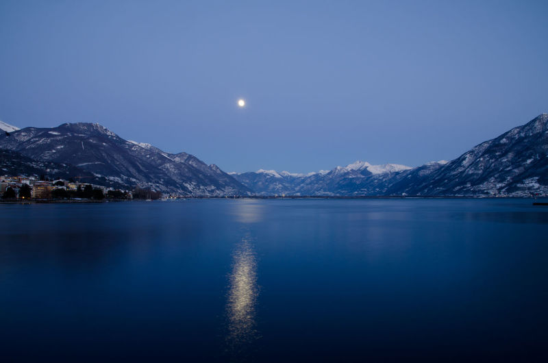 Scenic View Of Lake And Snowcapped Mountains Against Sky At Night