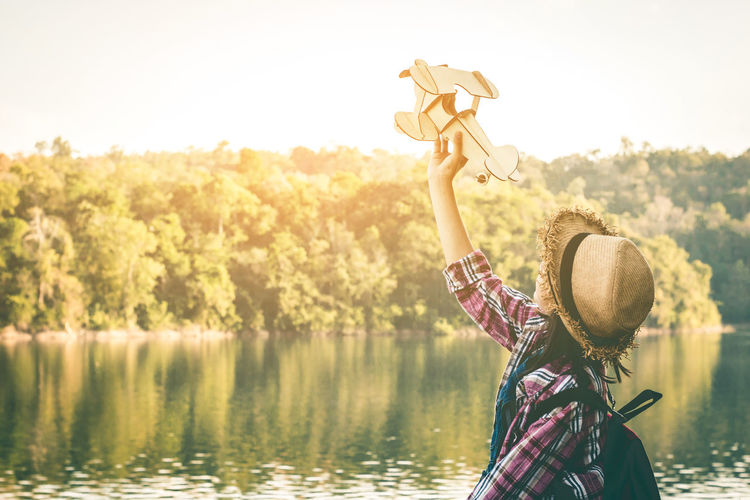 Girl holding model airplane while standing by lake