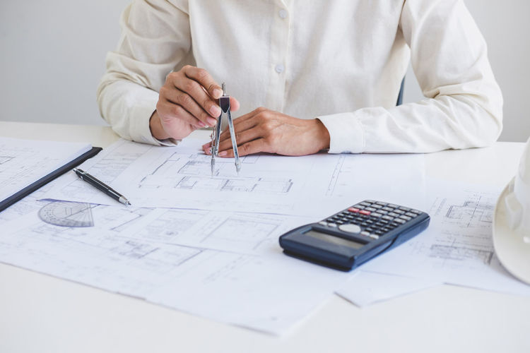 Midsection of architect making blueprint in office
