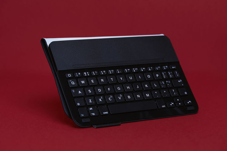 Black Wireless Bluetooth Tablet Keyboard on a Red Background Technology Computer Computer Equipment Red Indoors  Studio Shot Connection Business No People Keyboard Wireless Technology Red Background Colored Background Computer Keyboard Black Color Communication High Angle View Cut Out Number Single Object Silver Colored Computer Key