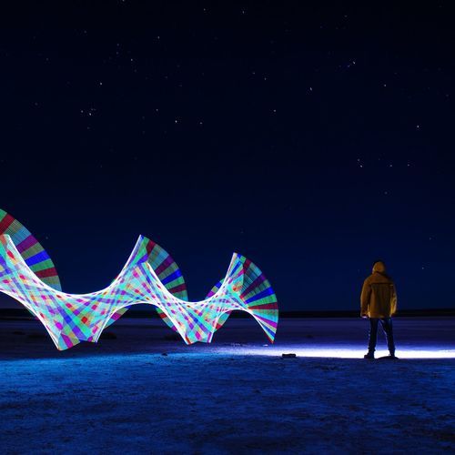 Rear view of man standing by light painting against sky at night