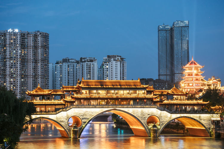 Arch bridge over river by buildings against sky in city