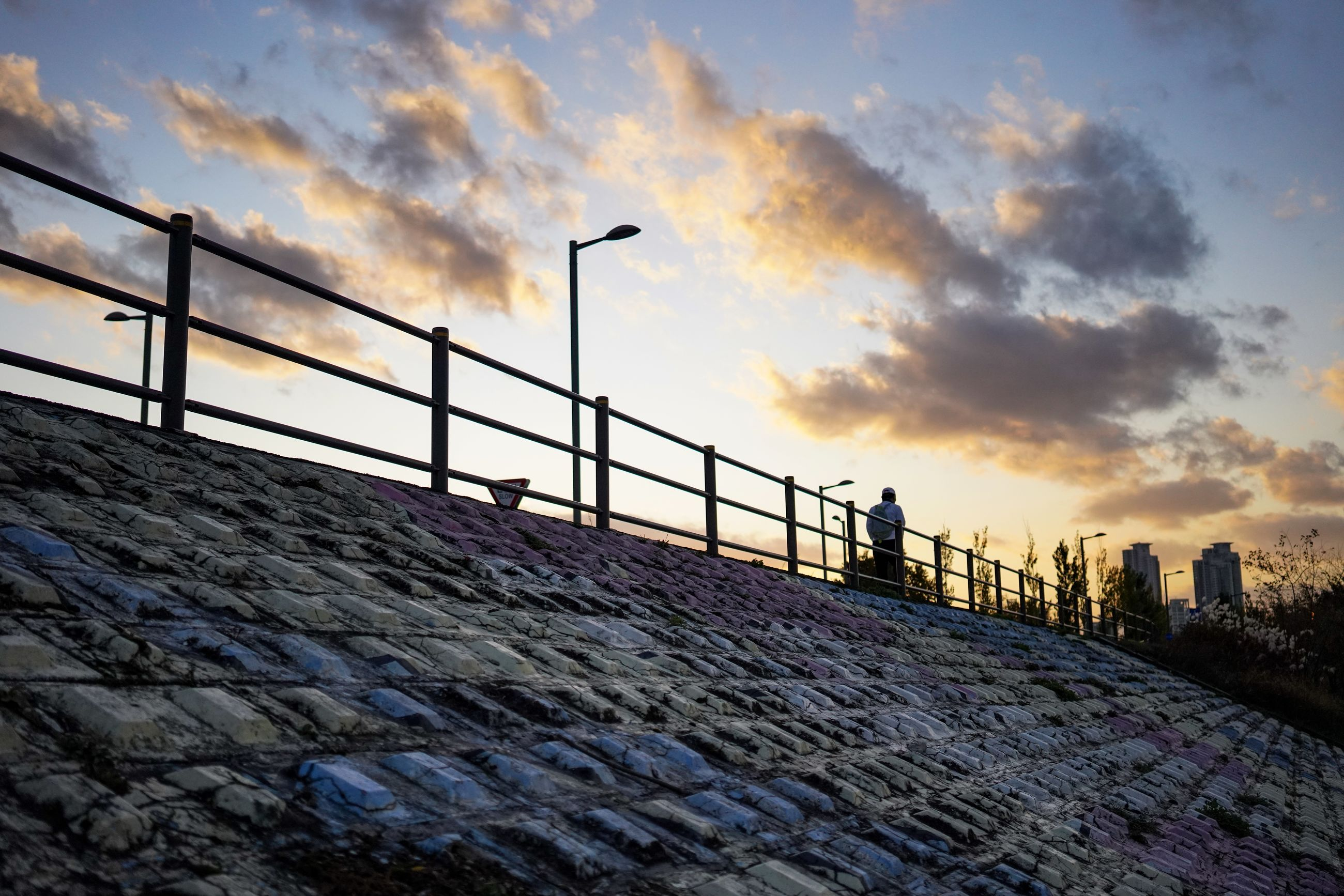 sky, cloud - sky, sunset, built structure, nature, architecture, real people, building exterior, leisure activity, lifestyles, wall, outdoors, standing, people, street, railing, men, city, scenics - nature