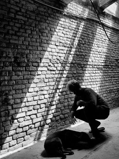 Man crouching by dog on footpath against wall