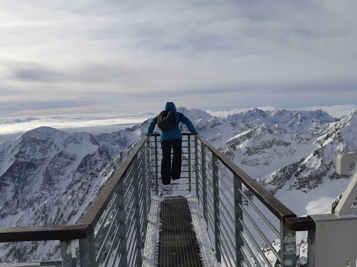 Rear view of man looking at snowcapped mountains while standing on observation point against sky