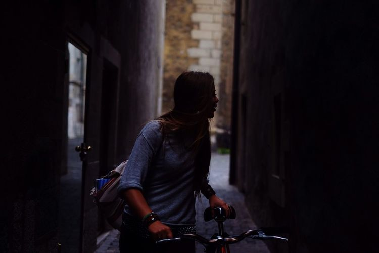 Young woman looking away while holding bicycle on street