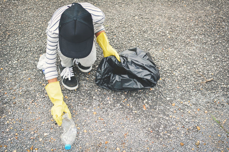 High Angle View Of Person Picking Crushed Bottle On Street