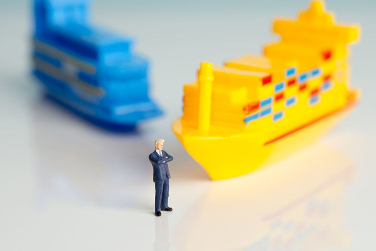 Miniature figures of a successful businessman with shipping background. Business Economy Industry Logistics Miniatures Tanker Transportation Businessman Cargo Cargo Container Commercial Corporation Freight Magnate Ship Shipping  Still Life Success Successful Technology Toy Traveller Tycoon Vessel ındustry
