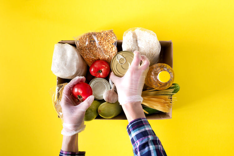 Close-up of hand holding toys against yellow background