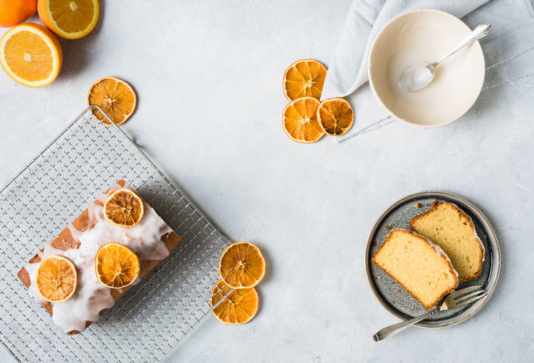 orange cake and orange cake slices with dried orangeslices beautiful placed on a bright grey surface from above | daylight foodphotography Dessert Desserts Food And Drink From Above  Homemade Nikon Orange StillLife Sugar Baked Bowl Bright Surface Cake Daylight Photography Dried Orange Food Food Photography Foodphotography Grey Homemade Cake No People Plate Slices