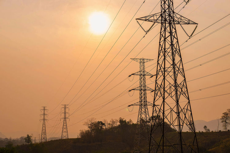 Low angle view of silhouette electricity pylon on field against sky during sunset