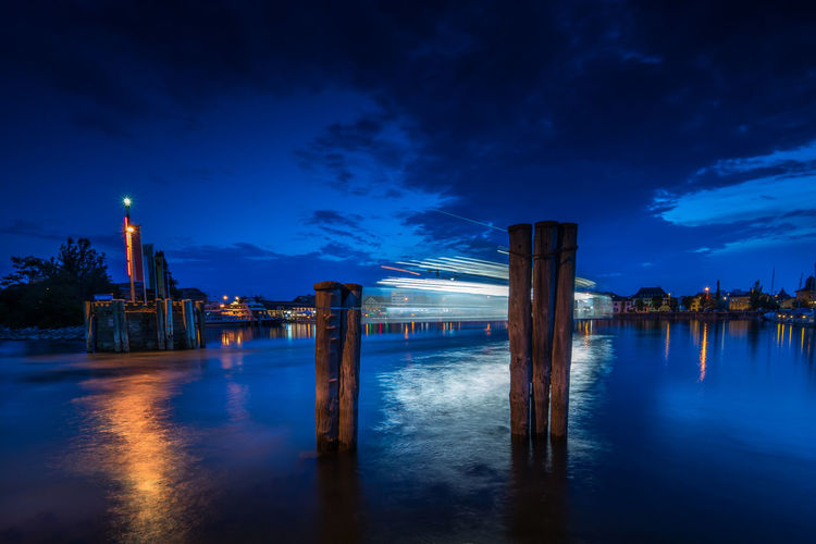 Illuminated wooden posts in lake against sky at night