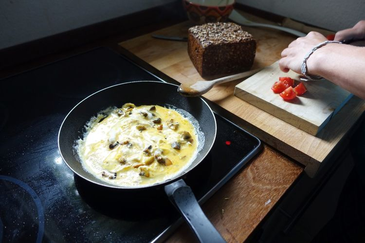Cropped Image Of Person Making Omelet In Kitchen
