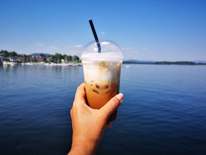 Hand holding glass of ice coffee