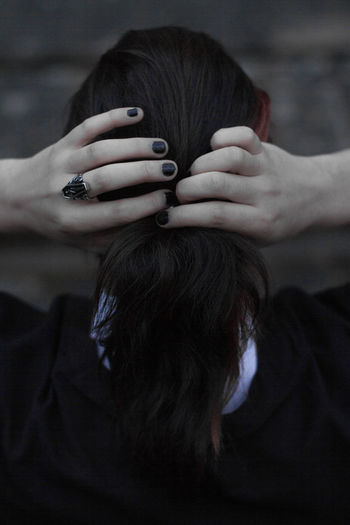 Rear view of woman tying hair