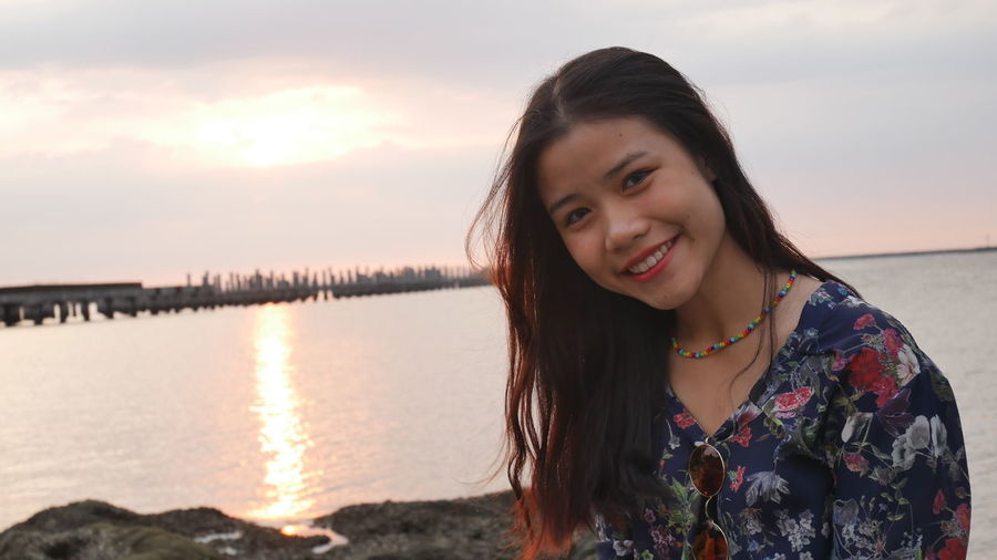 Portrait of smiling young woman at beach during sunset