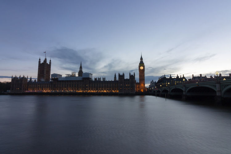Illuminated big bien and houses of parliament by thames river against sky