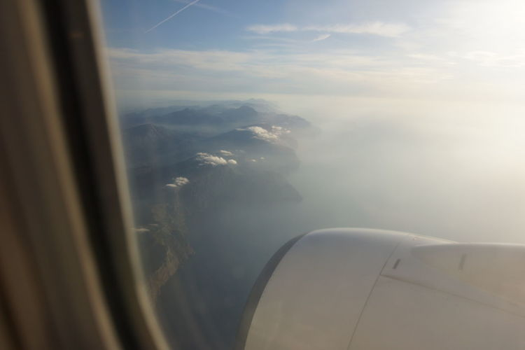 Aerial view of seascape seen through airplane window