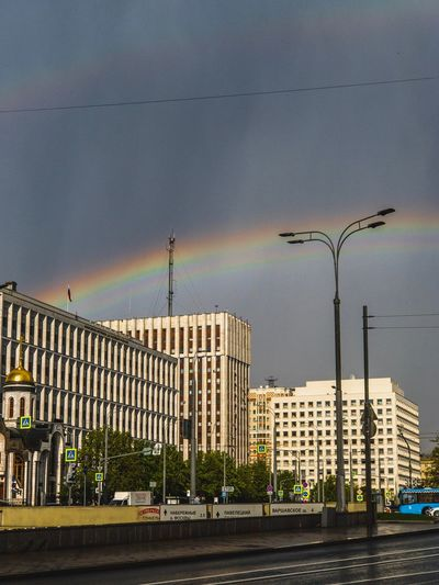 Rainbow Building Exterior Built Structure Architecture City Sky Street Street Light Day Outdoors Road Transportation Building Residential District Mode Of Transportation Cloud - Sky Nature No People Motor Vehicle Lighting Equipment Car