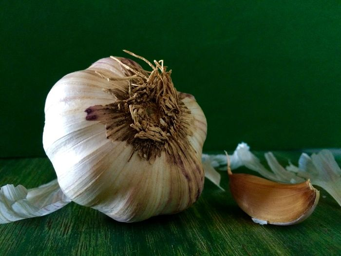 Close-up of garlic on table against green wall