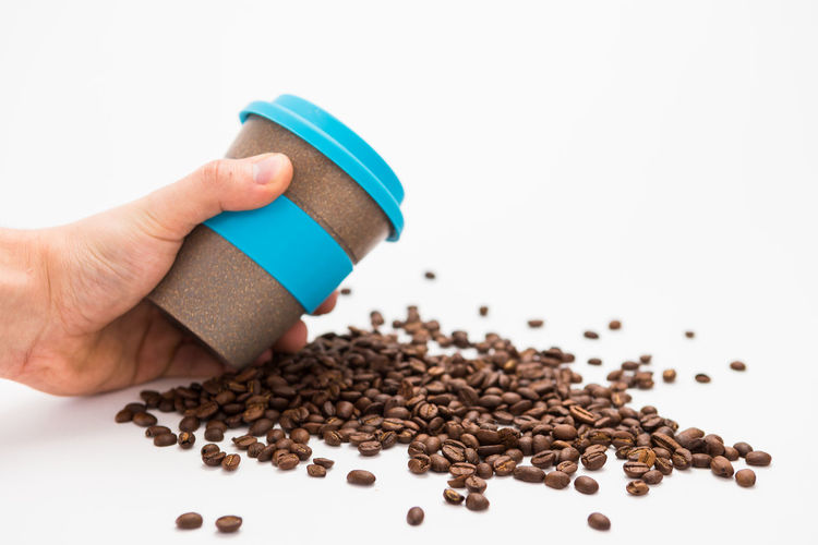 Man Holding Coffee cup to Go with Coffee Beans on the white Background Human Hand Hand Human Body Part White Background One Person Studio Shot Holding Indoors  Unrecognizable Person Food And Drink Finger Body Part Human Finger Real People Close-up Brown Lifestyles Food Large Group Of Objects Human Limb