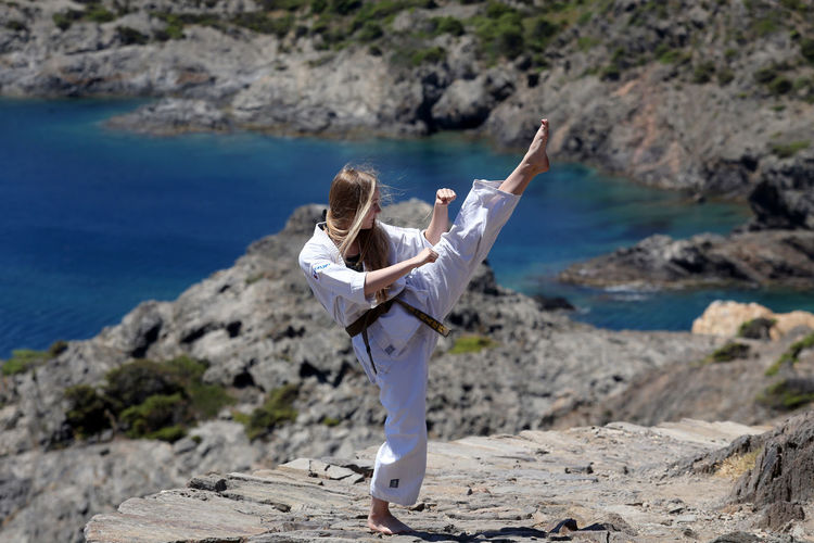Full length of woman practicing karate on rock against sea