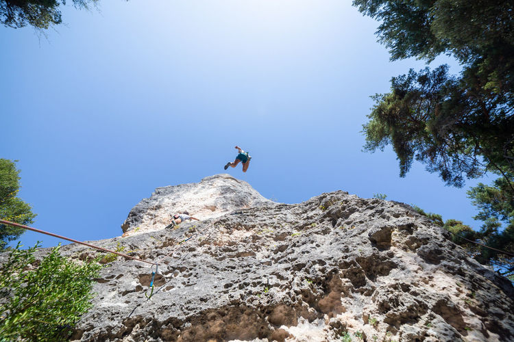Low angle view of male friends climbing on mountain against clear blue sky